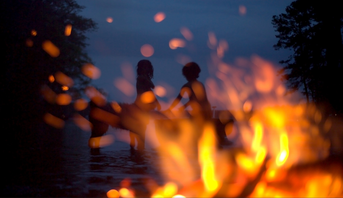 """Film still from Stansell's """"Over the Bent World"""" showing children on a lake bank with a campfire in the foreground"""