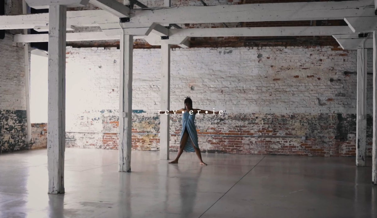 Dancer Raianna Brown poised to being dancing, feet spread and arms outstretched to the side