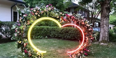 Two intersecting neon circles abbreviated to resemble a heart sitting on the ground outlined with flowers