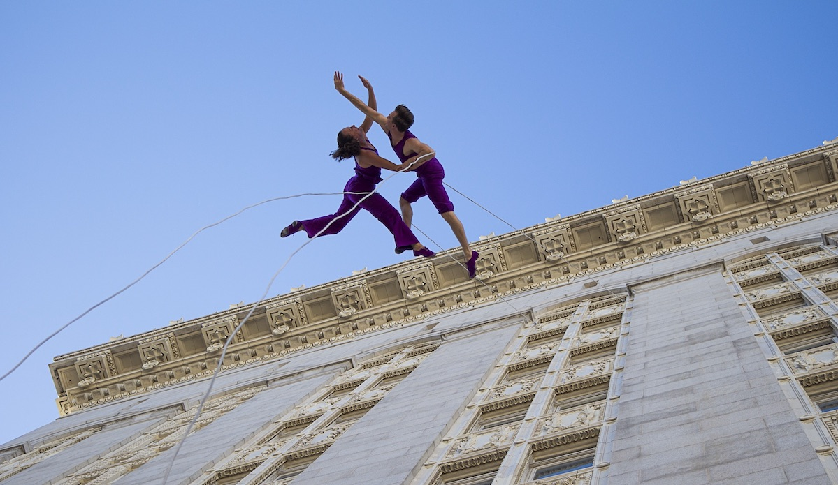 Two Bandaloop dancers performing on the side of Oakland City Hall